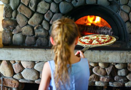 Un enfant faisant une pizza avec un four à bois