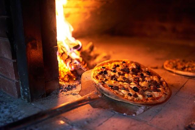 Des pizzas cuitent au feu de bois avec une cuisson convenable